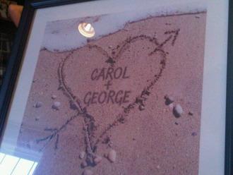 Κάδρο με μια χαραγμένη καρδιά στην άμμο με τα ονόματα της Καλομοίρας και του Γιώργου
