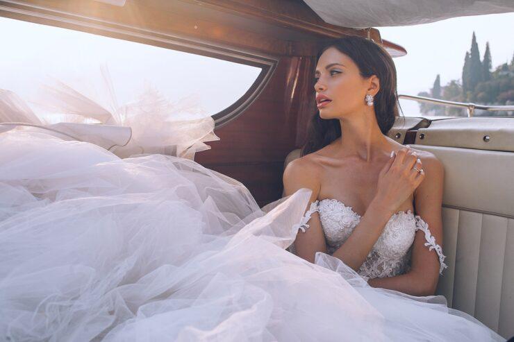 Νυφικό woman wearing white sweetheart-neckline wedding dress inside vehicle