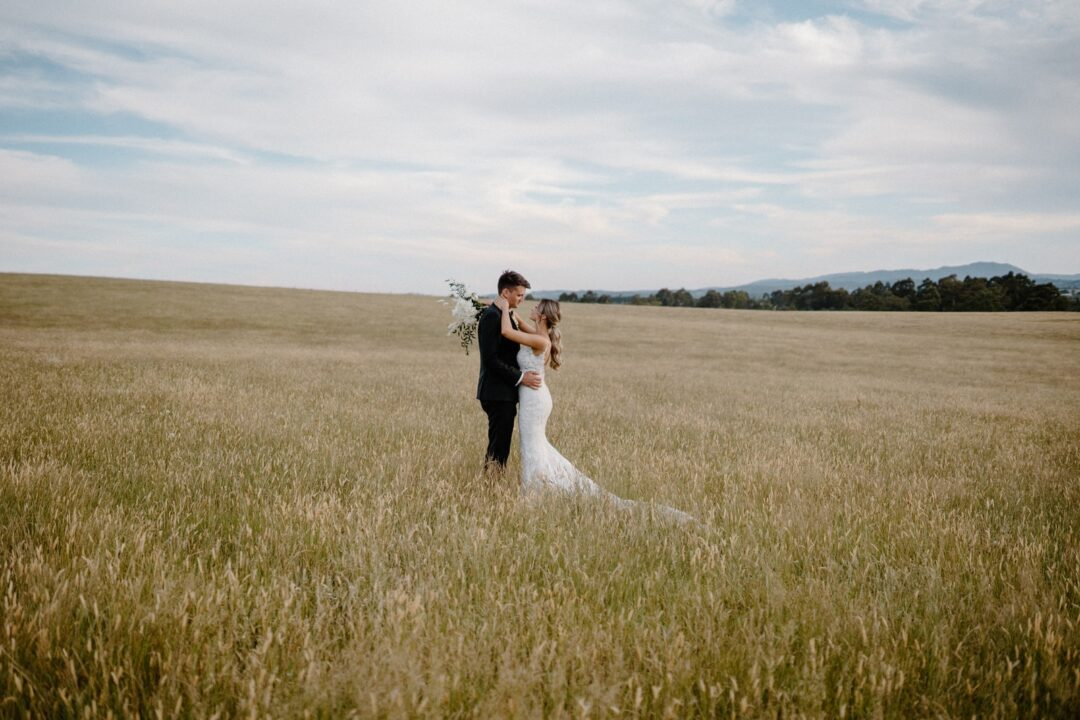 woman in white wedding gown holding man in black suit on green grass field during daytime