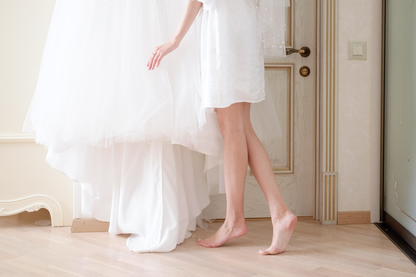 Αγορά νυφικού από το διαδίκτυο barefoot woman wearing white shirt standing near white dress