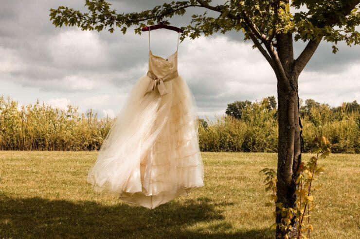 Νυφικό για την τέλεια μέρα white wedding dress hanging on green tree